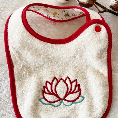 Bavoir à nouer bouton pression conçu avec tissy éponge écru et brodé avec une fleur de lotus