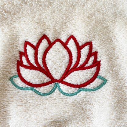 Zoom sur la broderie du bavoir à nouer bouton pression conçu avec tissy éponge écru et brodé avec une fleur de lotus