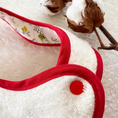 Zoom sur le bouton pression du bavoir à nouer bouton pression conçu avec tissy éponge écru et brodé avec une fleur de lotus