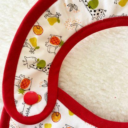 Zoom sur le bouton pression du bavoir à nouer bouton pression conçu, avec popeline animaux et fruits