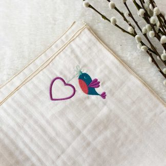 Zoom sur la broderie oiseau et coeur du lange tissu écru