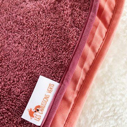 Zoom sur tapis de change ouvert, tissu éponge bordeaux et tissu chambray corail