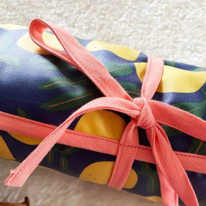 Tapis de change fermé, tissu laminé motif citrons avec biais corail