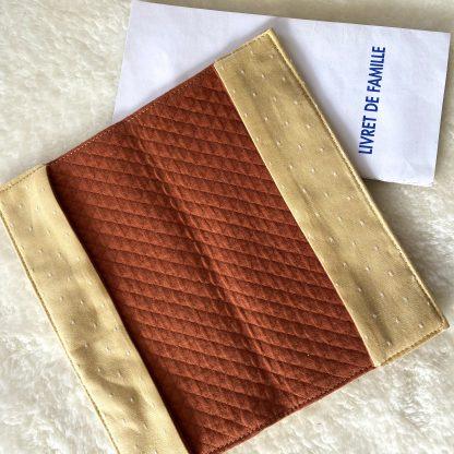 Protège livret de famille en tissus chambray jaune à pois blanc pour l'extérieur et les rabats, et intérieur en tissu jersey matelassé couleur rouille