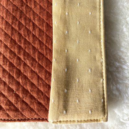 Zoom sur le revers du Protège livret de famille en tissus chambray jaune à pois blanc pour l'extérieur et les rabats, et intérieur en tissu jersey matelassé couleur rouille