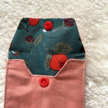 Zoom sur la Housse de transport pour brosses à dents en tissu chambray corail et tissu hydrofuge bleu avec roses rouges à l'intérieur et bouton pression rouge