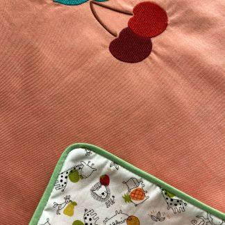 Recto/Verso de la Housse de coussin en tissu chambray corail, passepoil vert et verso en tissu popeline animaux et fruits, avec une broderie cerises