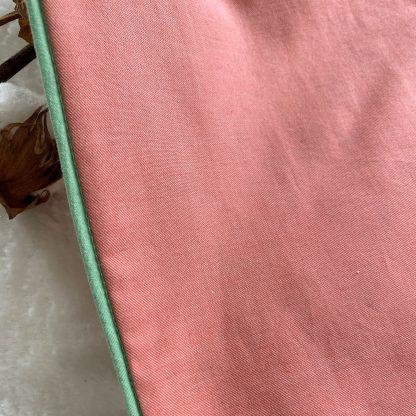 Zoom sur le passepoil de la Housse de coussin en tissu chambray corail, passepoil vert et verso en tissu popeline animaux et fruits, avec une broderie cerises