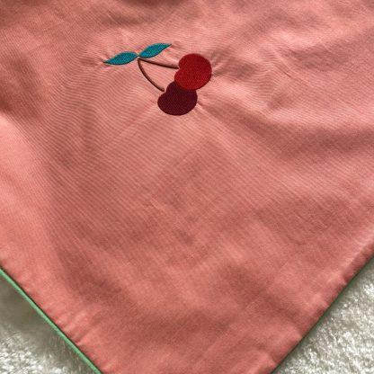 Housse de coussin en tissu chambray corail, passepoil vert et verso en tissu popeline animaux et fruits, avec une broderie cerises