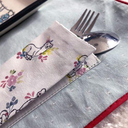Zoom sur le range couverts du Set de table en tissu chambray bleu ciel à pois blanc et vers en tissu hydrofuge bleu à roses rouges avec passepoil rouge